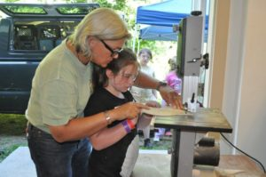 Elaine Hamel of Girls At Work teaches Arianna Laliberte how to use a table saw. Photo by Keith Testa / Concord Insider Staff